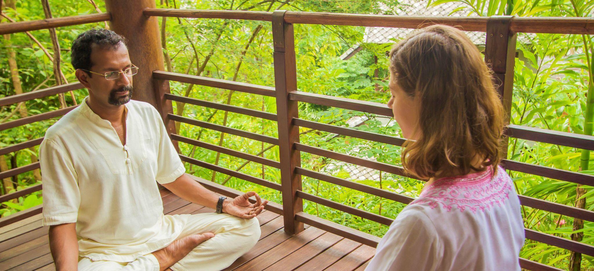 Mann und Frau Meditieren hoch in den Bäumen im Hotel Kamalaya, Thailand