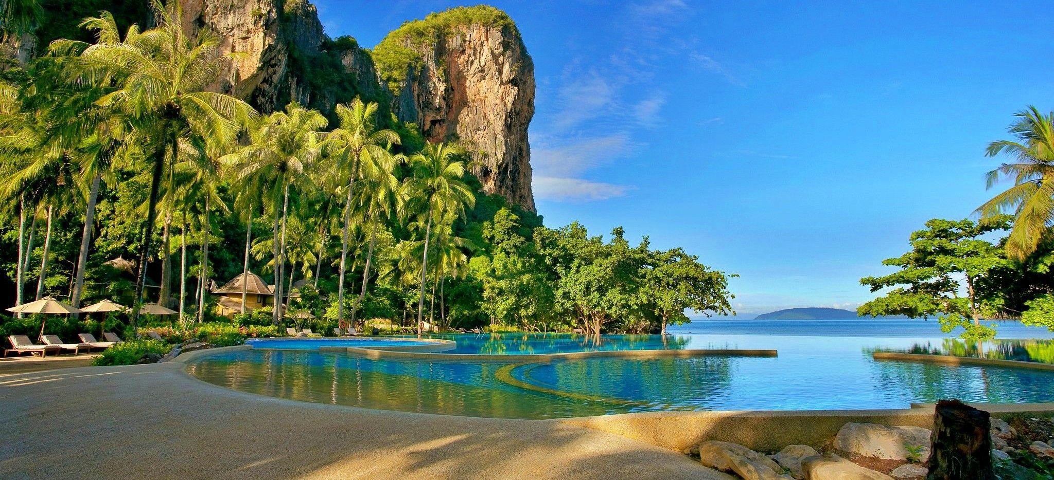 Ein Pool umgeben von Palmen und riesigen Felsen mit Blick auf das Meer