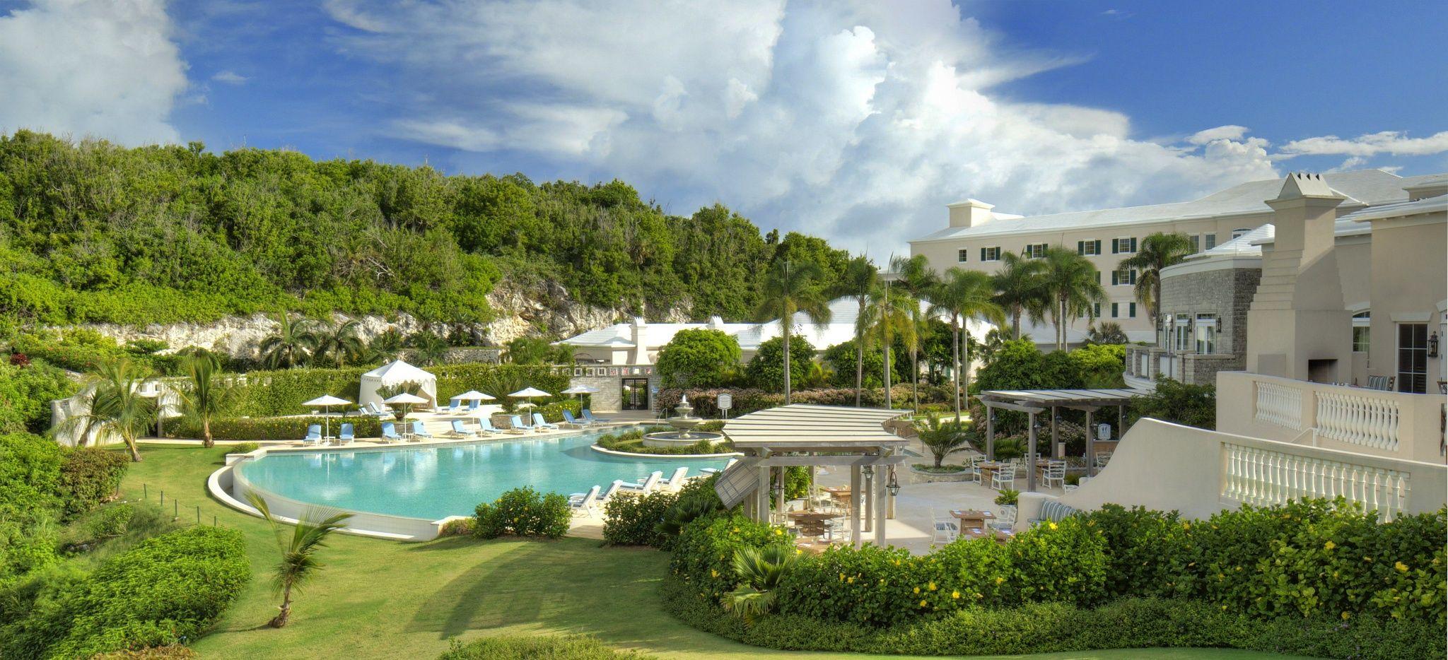 """Ein Tal mit einem Pool in der Mitte und dem Hotel """"Rosewood Tucker's Point"""" darum herum"""