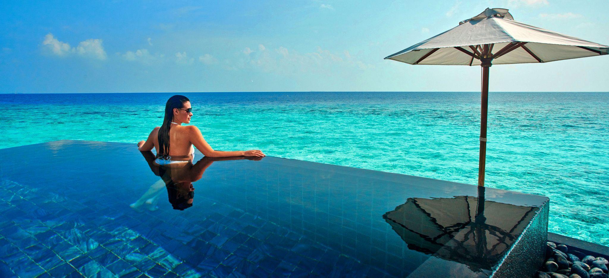 Eine Frau schwimmt in einem privaten Pool einer Wasservilla in der Lagune des Hotels Constance Halaveli