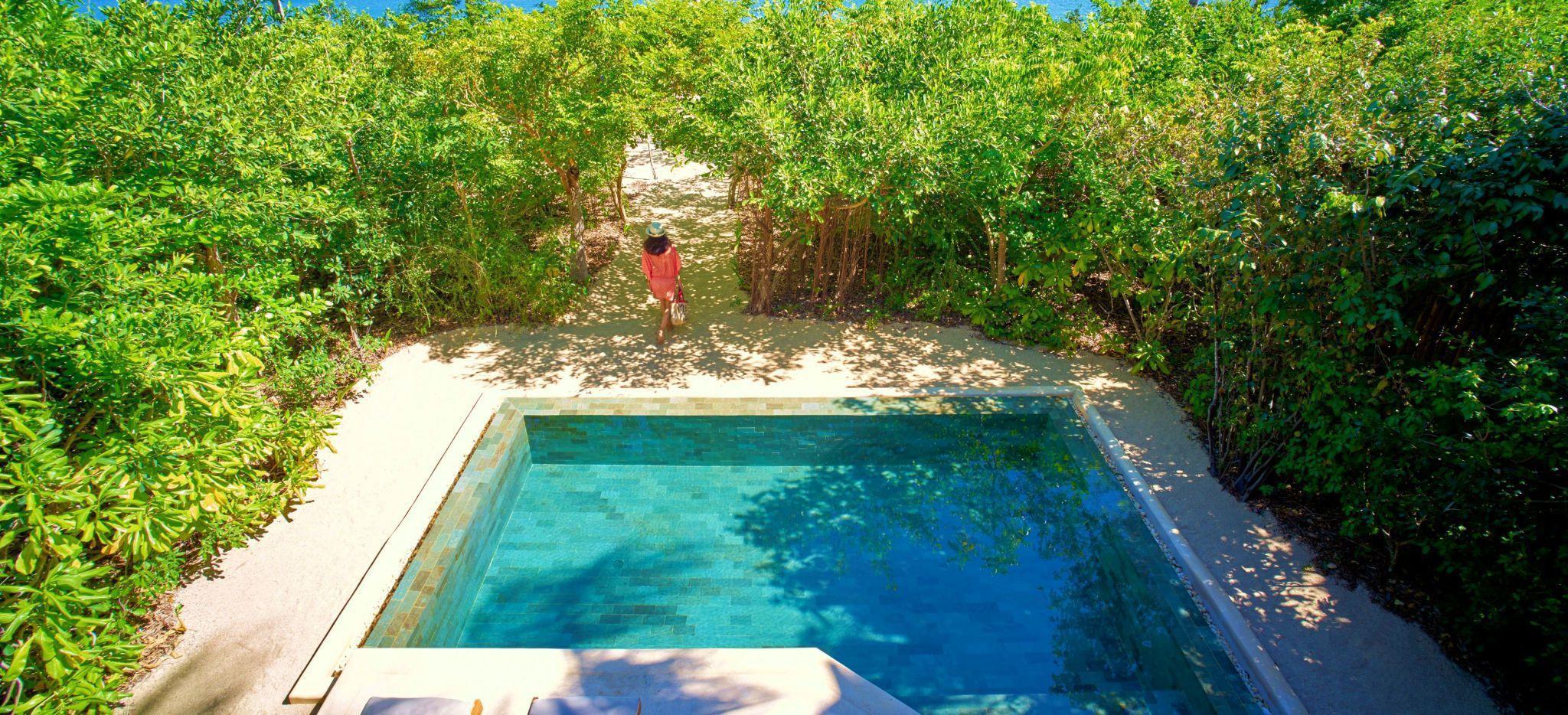 Ein von tropischem Gestrüpp umgebener Pool mit einem kleinen Weg zum Strand