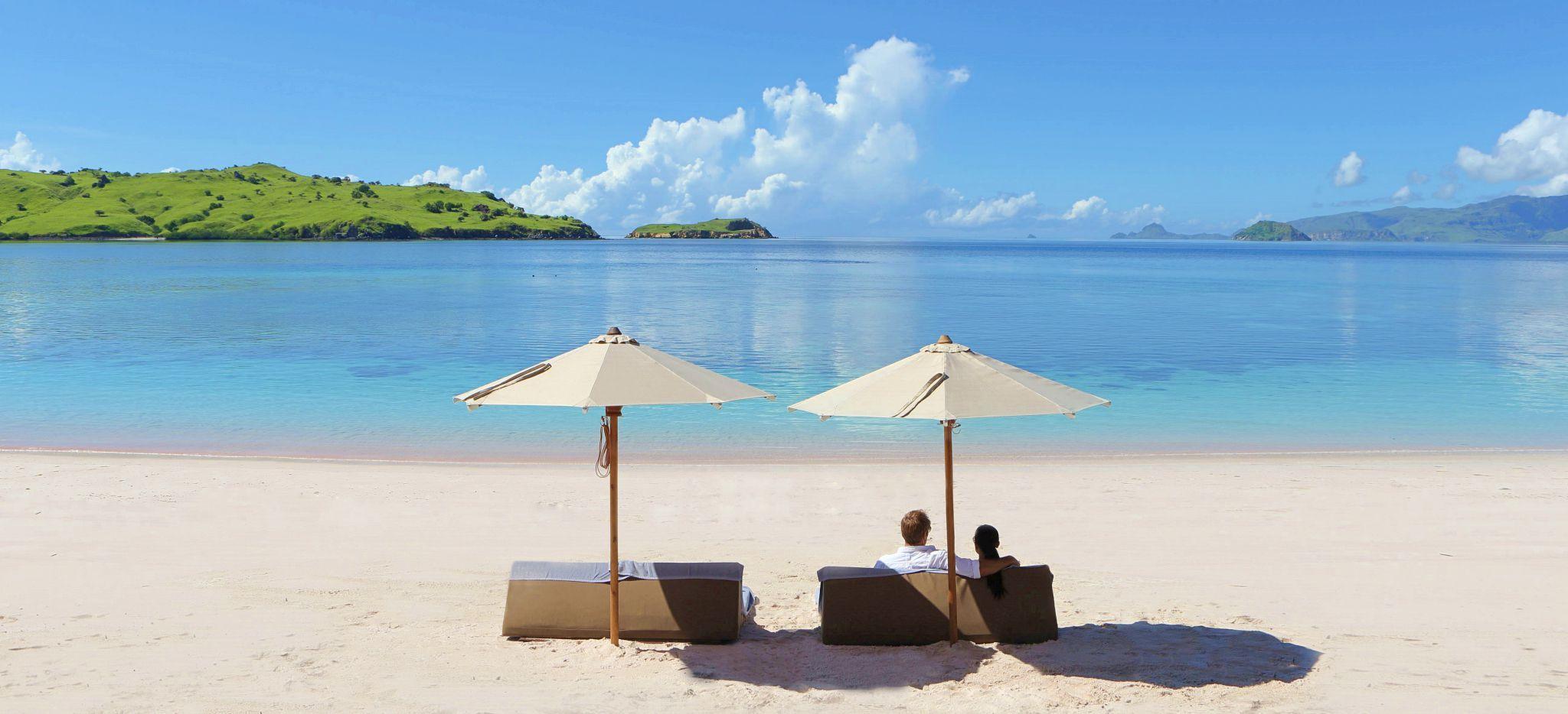 Paar auf Strandliegen am Strand, Blick auf das Meer und Inseln in der Ferne