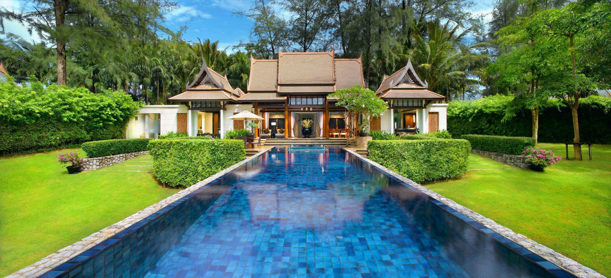 Ein sehr langer Pool, der zu einem Hotelgebäude im Stil eines Thailändischen Tempels