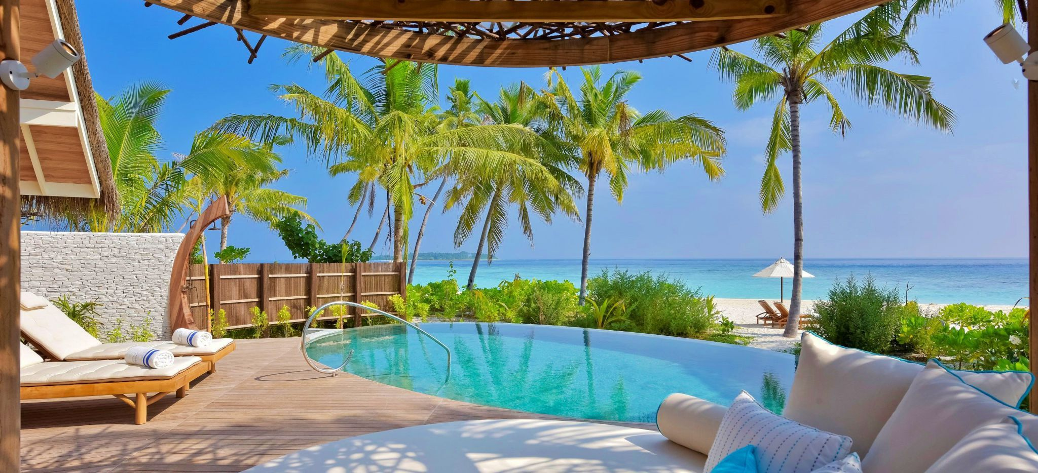 Meerblick von der Terrasse eines weitläufigen, freistehenden Hotelzimmers, über einen Pool und den Strand
