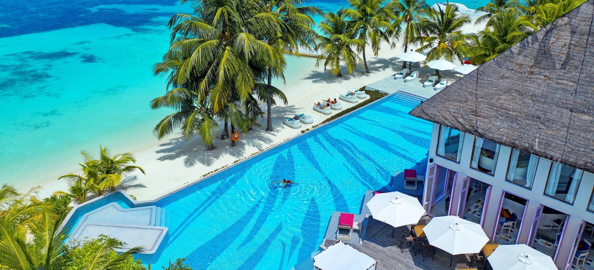Ein großer Pool direkt am Strand vor einem Restaurant auf der Malediveninsel Madhoo