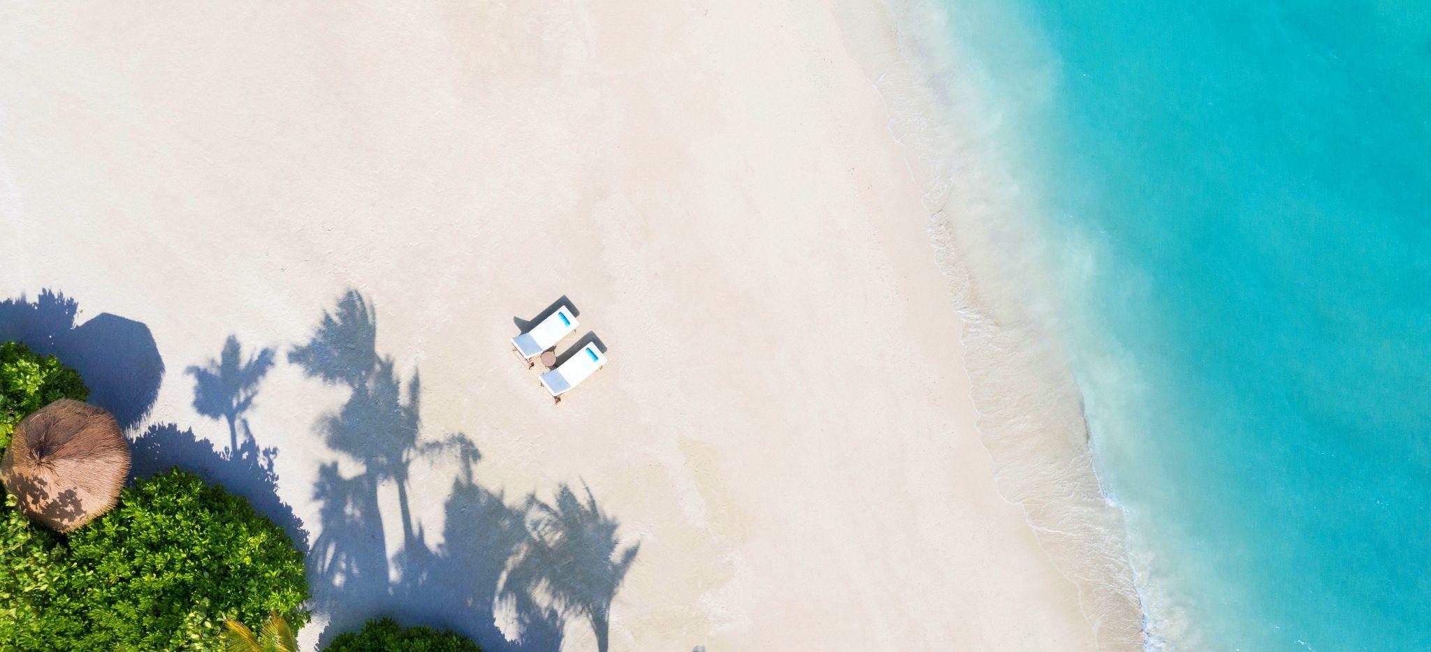 Ein Privater Strand mit zwei Strandliegen im Waldorf Astoria Maldives, mit ein wenig tropischem Grün