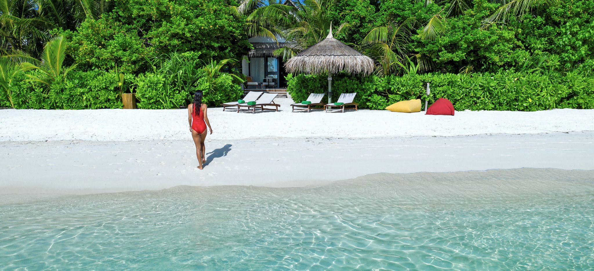 Eine Frand wandert am weißen Strand einer Malediveninsel. Das Hotelzimmer Earth Pool Pavillon im Hotel OZEN.