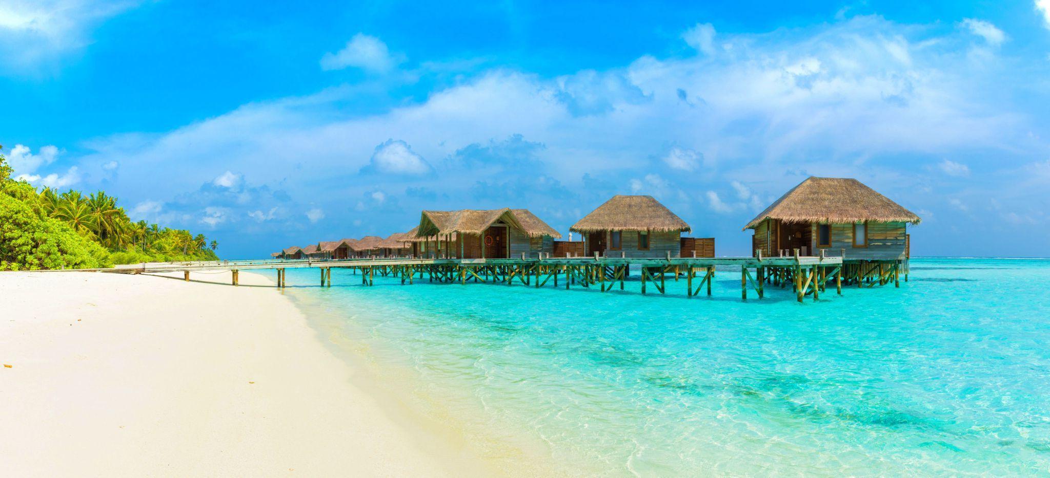 Ein Strand der Insel Conrad Rangali Maldives mit mehreren Wasservillen vorgelagert