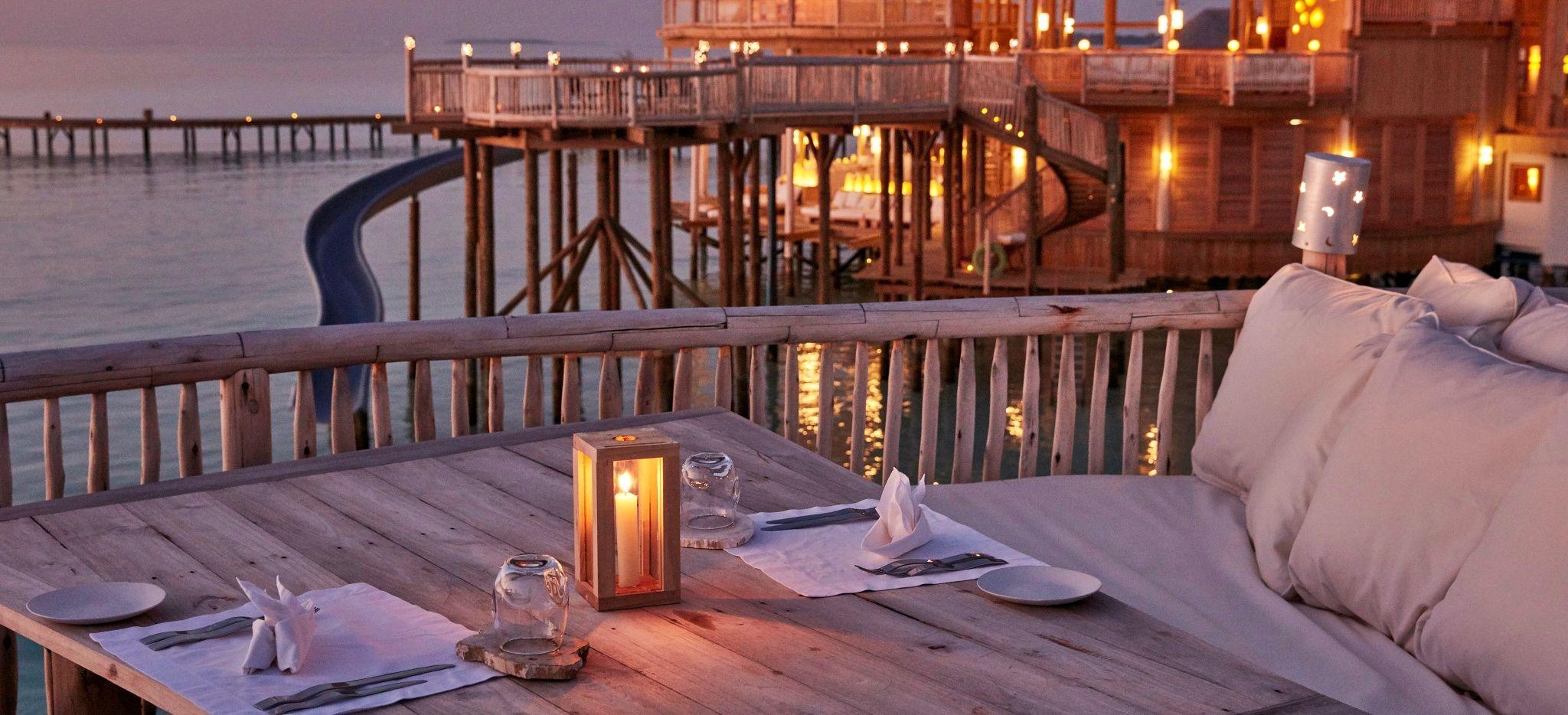 """Ein Dinner-Tisch mit Blick auf das Hauptgebäude des Hotels """"Soneva Jani"""""""