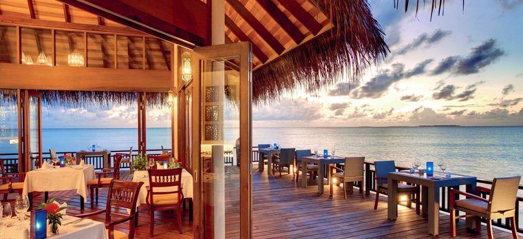 Ein Restaurant auf Stelzen im Meer, viele Tische sind gedeckt