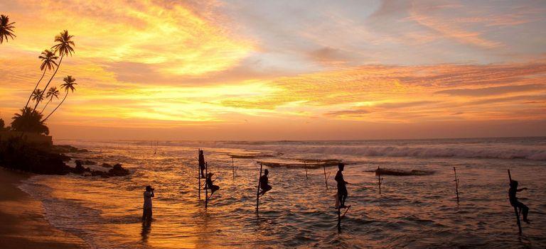 Fischer auf Stelzen am Strand im Abendrot, Sri Lanka