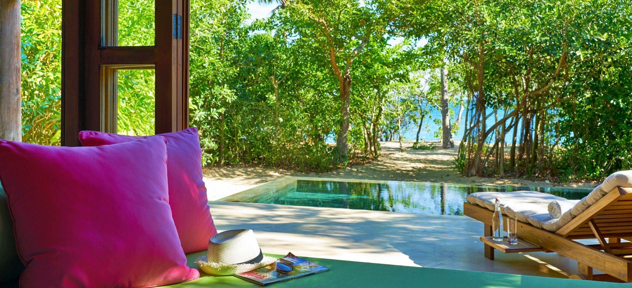 Eine Terrasse mit einem Privatem Pool und einem Zugang zum Strand
