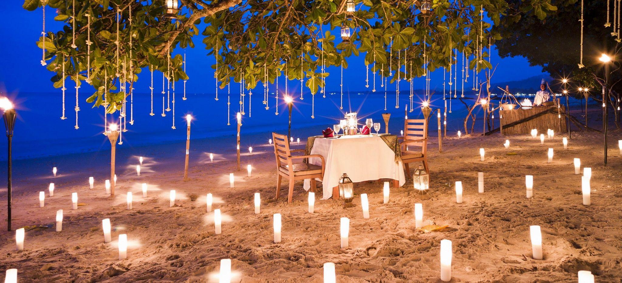 """Ein Strand mit brennenden Kerzen, dazwischen ein Dinner Tisch. Im Hotel """"The Sarojin"""""""