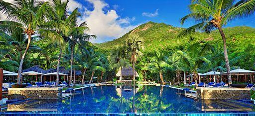 """Der Hauptpool des Hilton Labriz mit dem Berg """"Mont Plaisier"""" auf Silhouette im Hintergrund, Seychellen"""