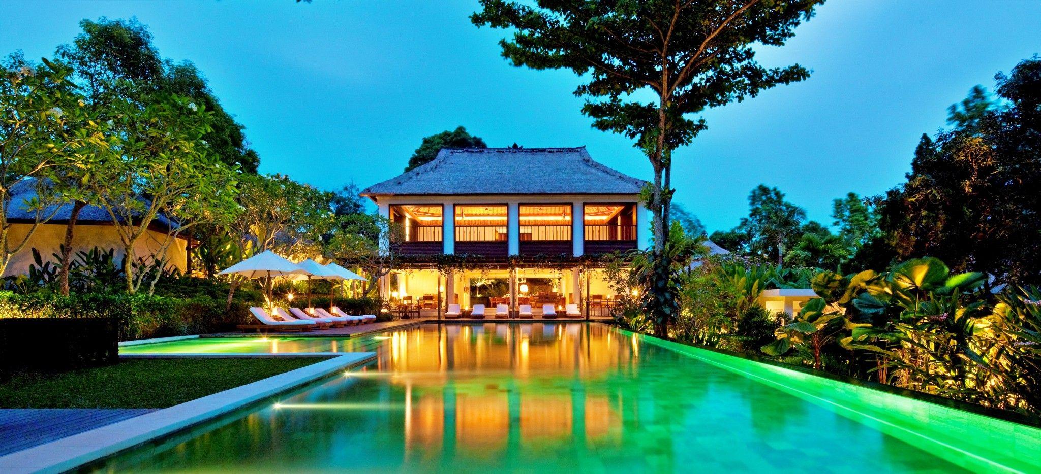 """Ein beleuchteter Pavillion am Ende eines langen Pools im Hotel """"COMO Uma Ubud"""" in Bali"""