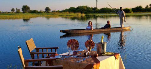 Paar mit Guide in Kanu, am Ufer ist ein Tisch für zwei gedeckt