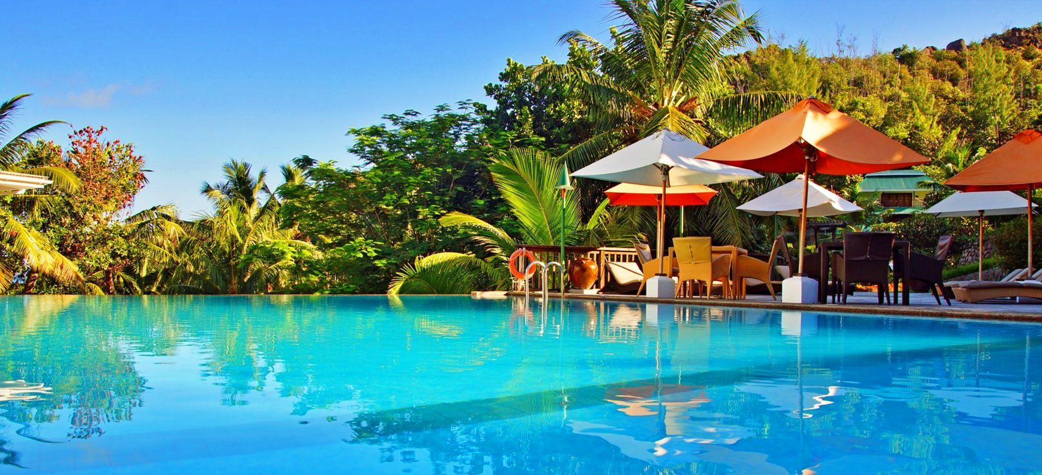 Ein großer Pool nah über der Oberfläche, dahinter Sonnenschirme