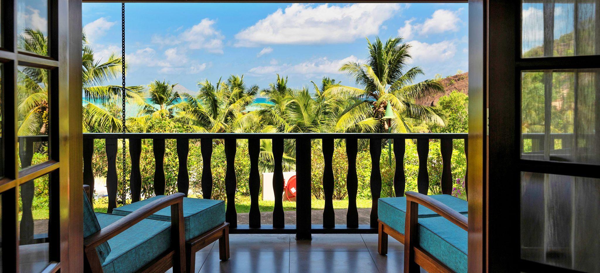 Zwei Strandliegen auf einem Balkon mit Blick auf einen Palmengarten