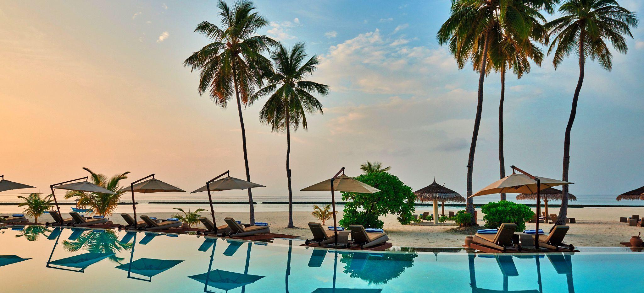 Ein Pool mit Blick auf den Strand und das Meer einer Malediveninsel