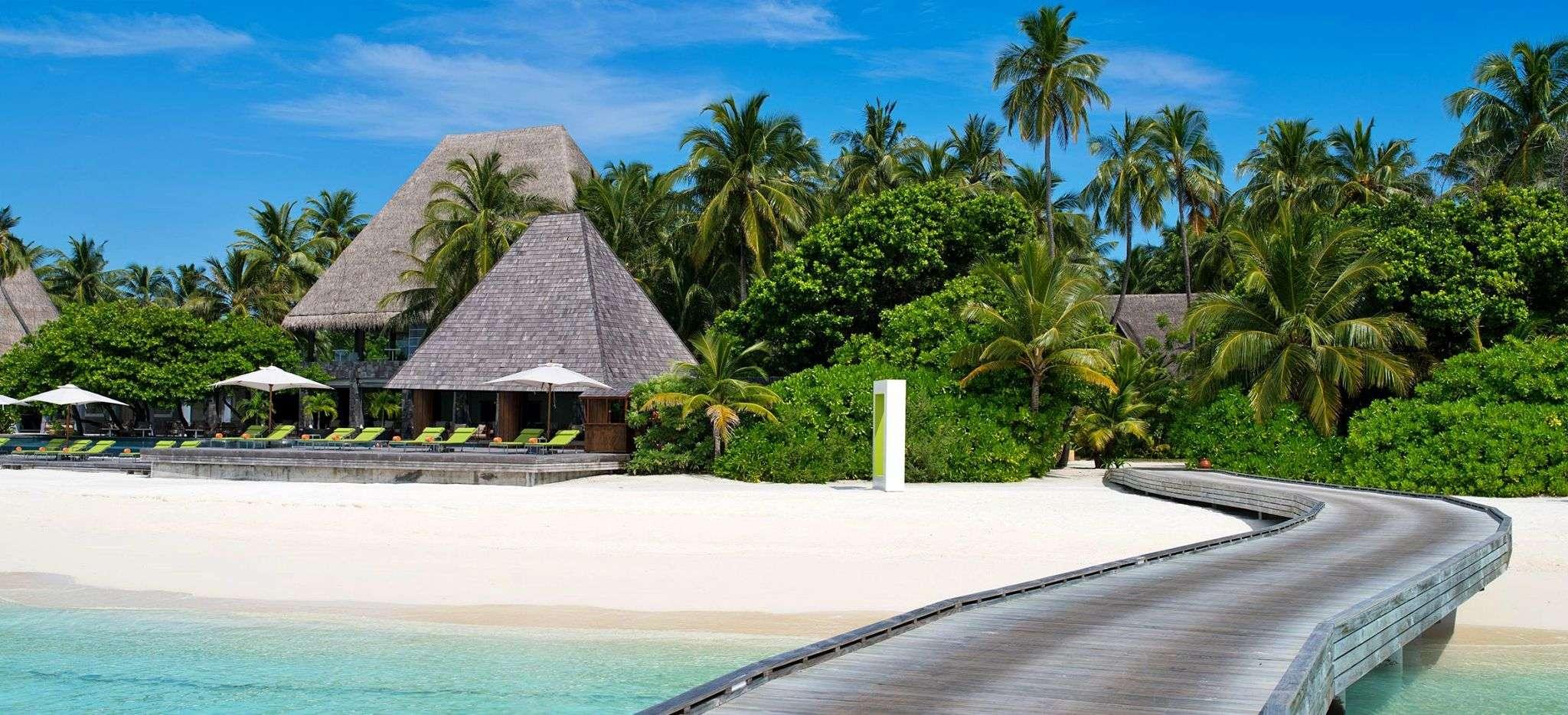 Ein Steg an einer Malediveninsel, Blick auf den Strand und mit Palmblättern gedeckte Häuser. Das Hotel Anantara Kihavah