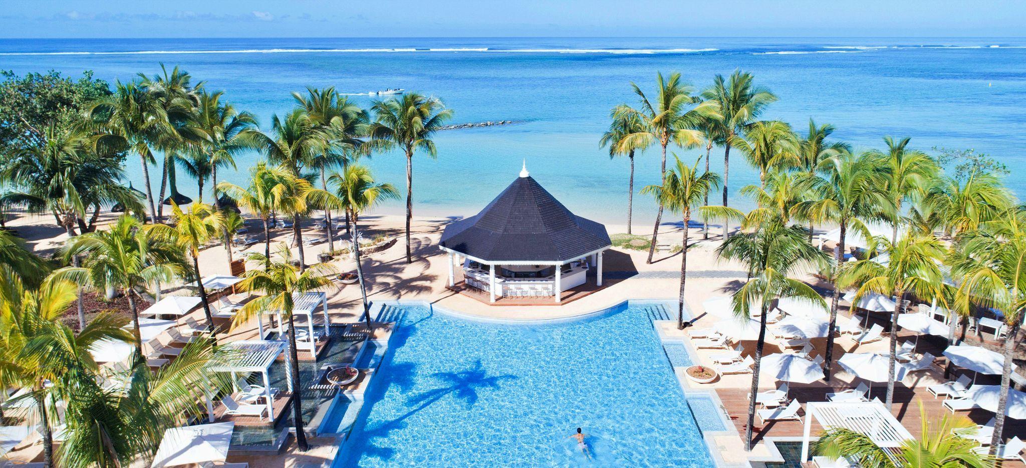 Ein Pool in einer Palmen Allee richtung Meer auf Mauritius