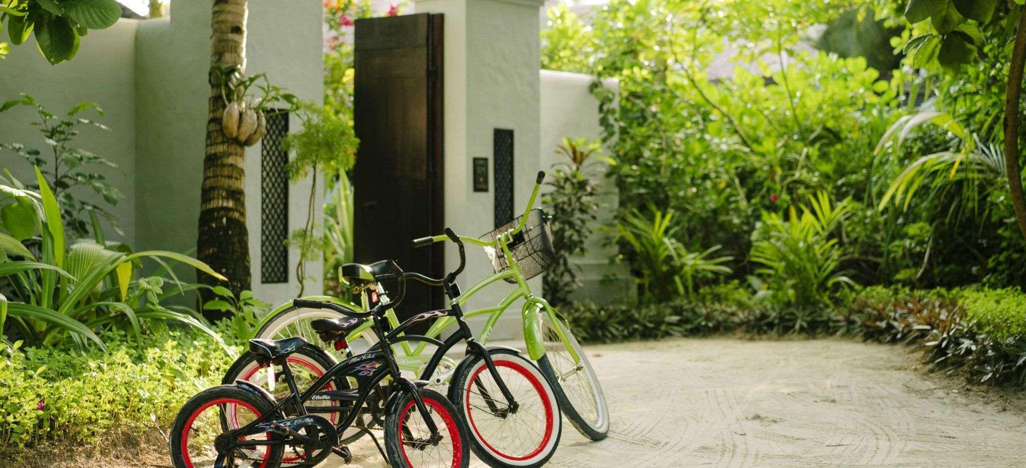 Vier Fahrrader vor dem Eingang einer Beach Residence im Anantara Kihava