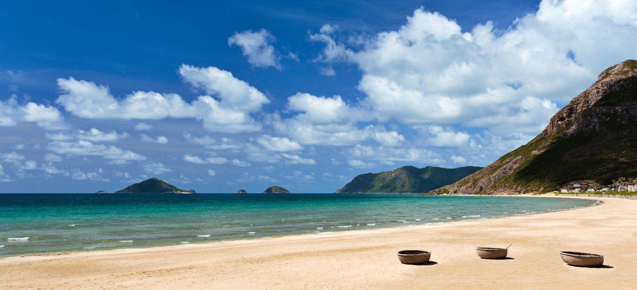 Ein langer Strand in Vietnam, mit Blick auf vorliegende Inseln im Meer