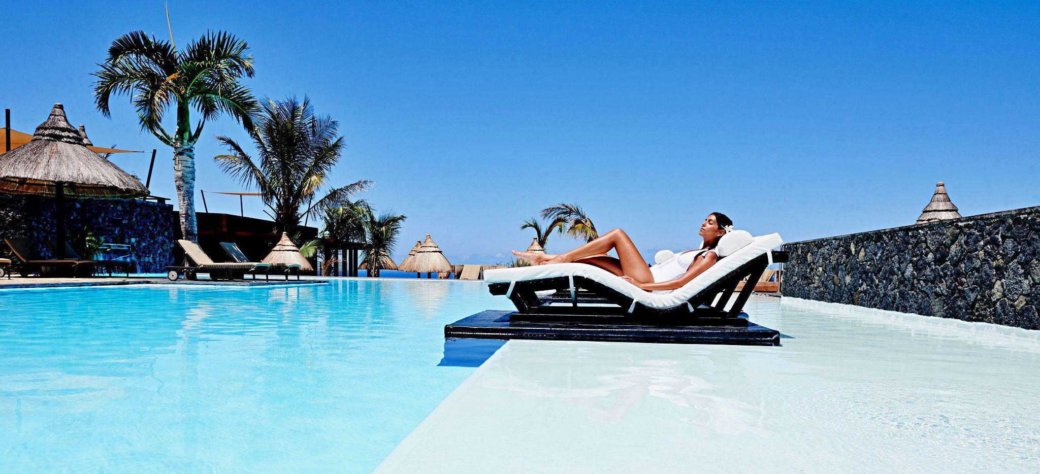 Eine Frau liegt auf einer Liege am Pool des Hotels Palm auf La Réunion