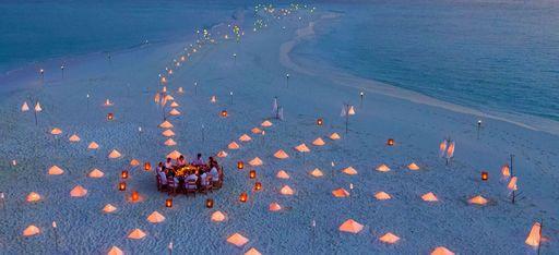 Sandbank von Soneva Fushi dekoriert mit Lichtern für ein Privates Abendessen vorbereitet