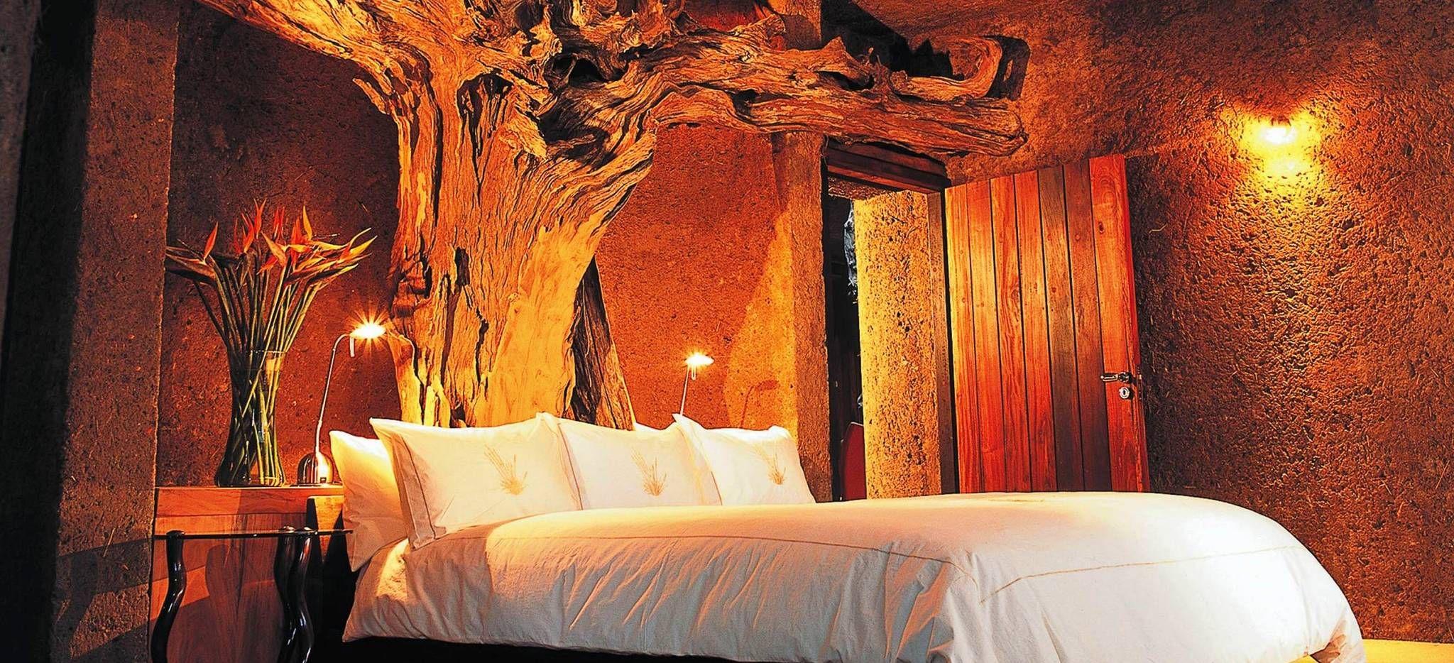 Bett mit eingebautem Holzstamm am Kopfende, das Hotelzimmer Amber Suite im Hotel Earth Lodge