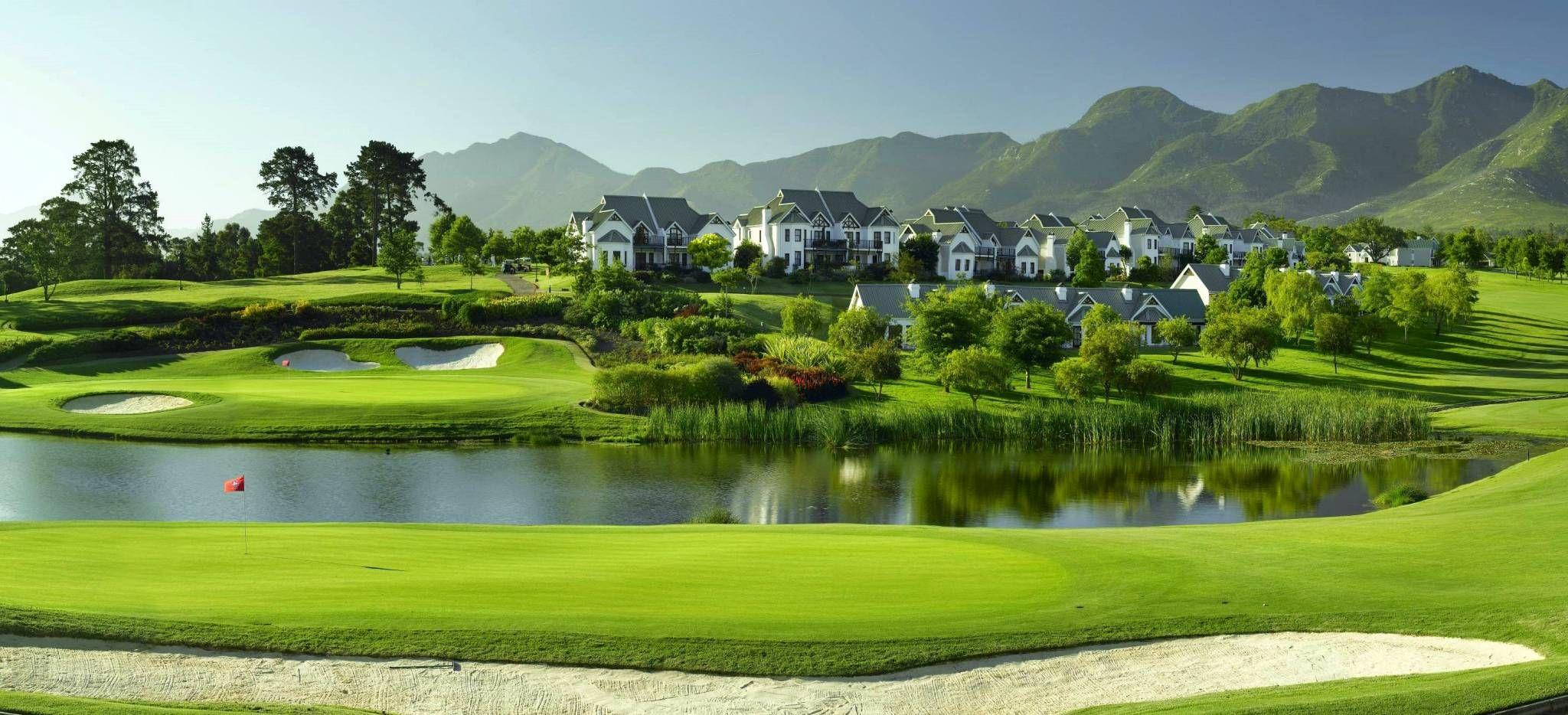 Golfplatz mit ausladenden Teichen vor einer Bergkulisse in Südafrika