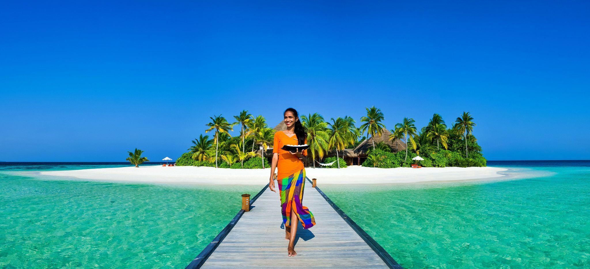Eine Frau in buntem, maledivisch gebundenem Sahrong läuft auf dem Steg der Malediveninsel Mirihi