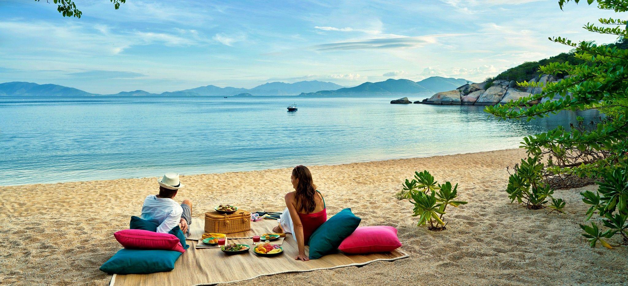 Ein Paar genießt ein Luxuriöses Picnic am Strand des Six Senses Ninh van Bay
