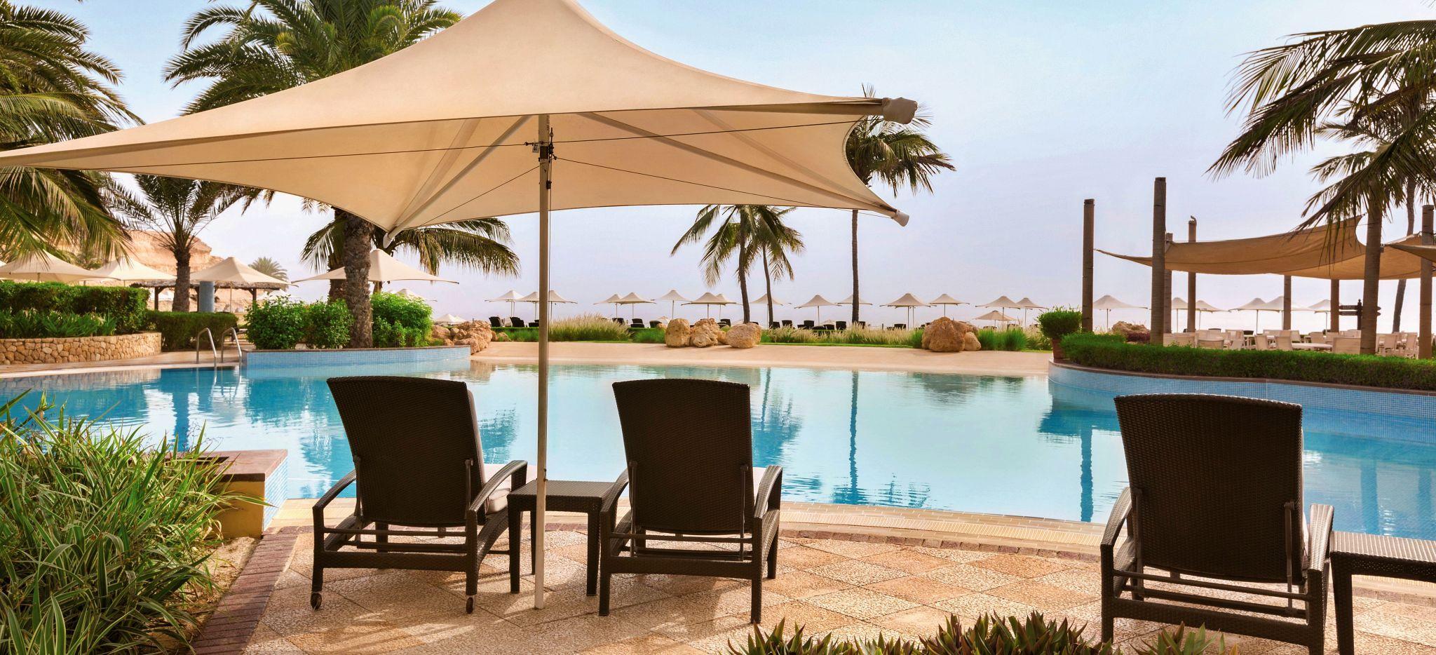 Pool mit Palmen und Sonnenschirmen und -stühlen im Shangri-La Barr Al Jissah Al Bandar Resort nahe Maskat, Oman