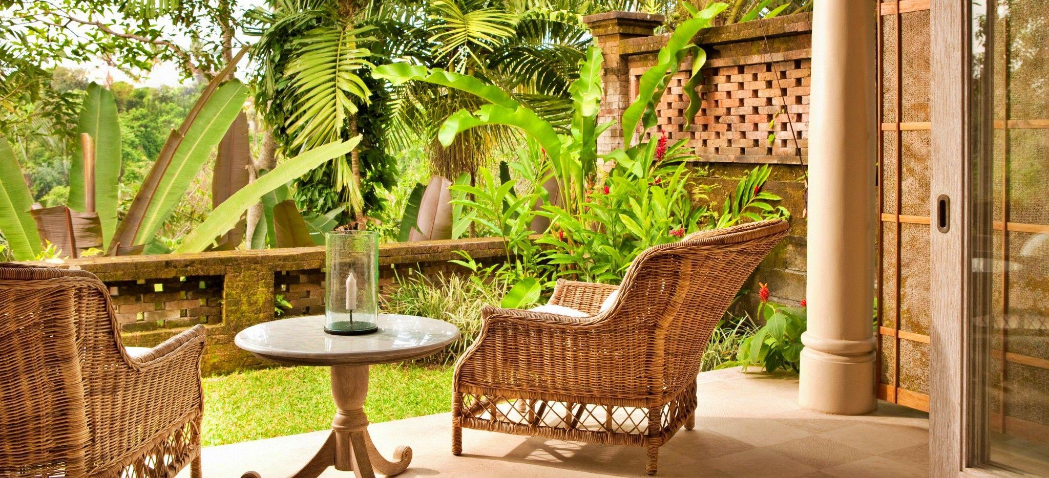 Eine Terrasse mit zwei Rattan-Sesseln mit Blick auf einen balinesischen Garten