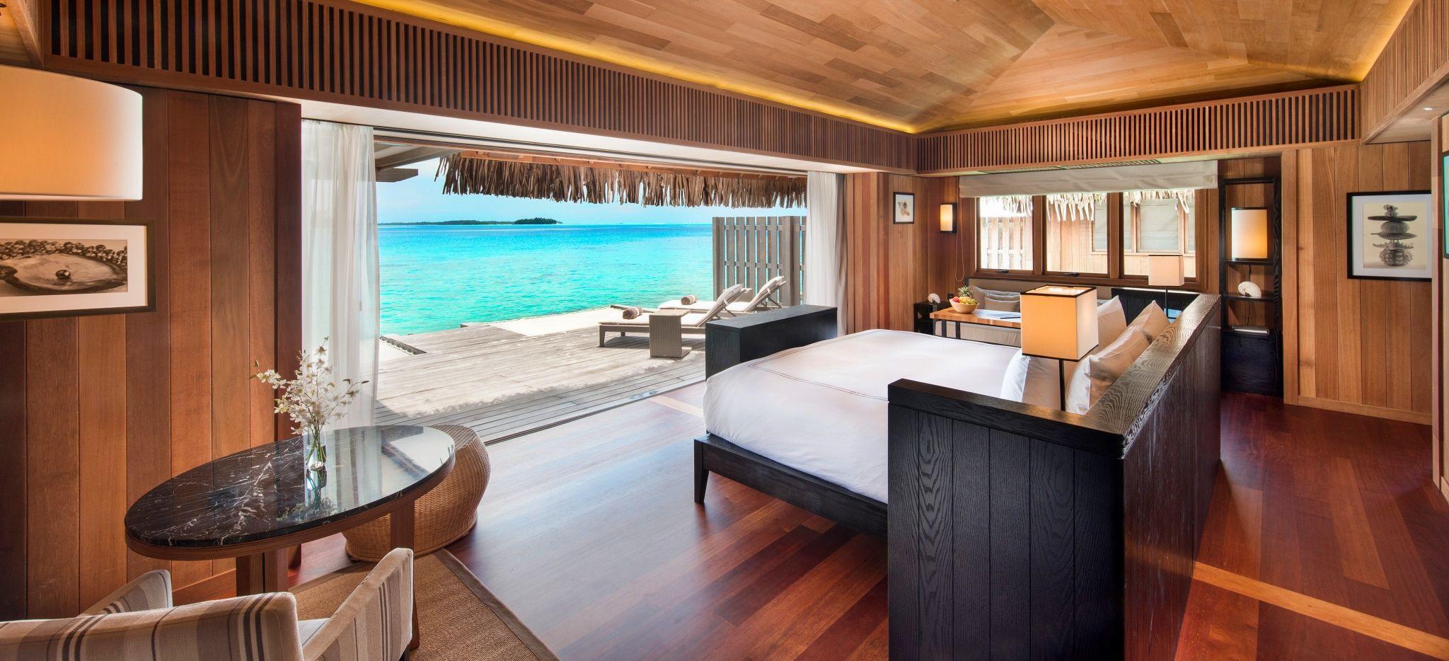 """Ein mit dunklem Holz verkleidetes Schalfzimmer einer Wasservilla des Hotels """"Conrad Bora Bora Nui"""""""