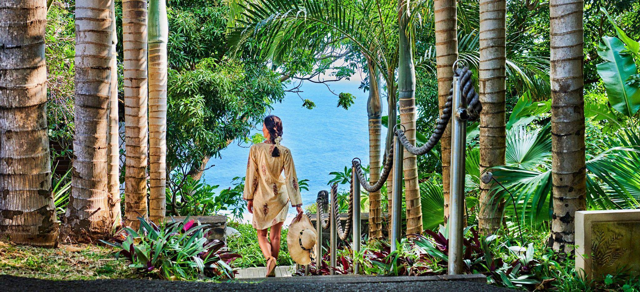 Eine Frau läuft die Treppen zwischen Palmen zu Meer im Hotel Palm auf La Réunion