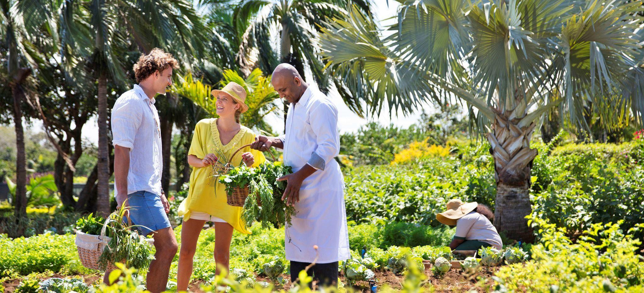 Ein Paar steht mit einem Hotelangestellten in einem Kräutergarten