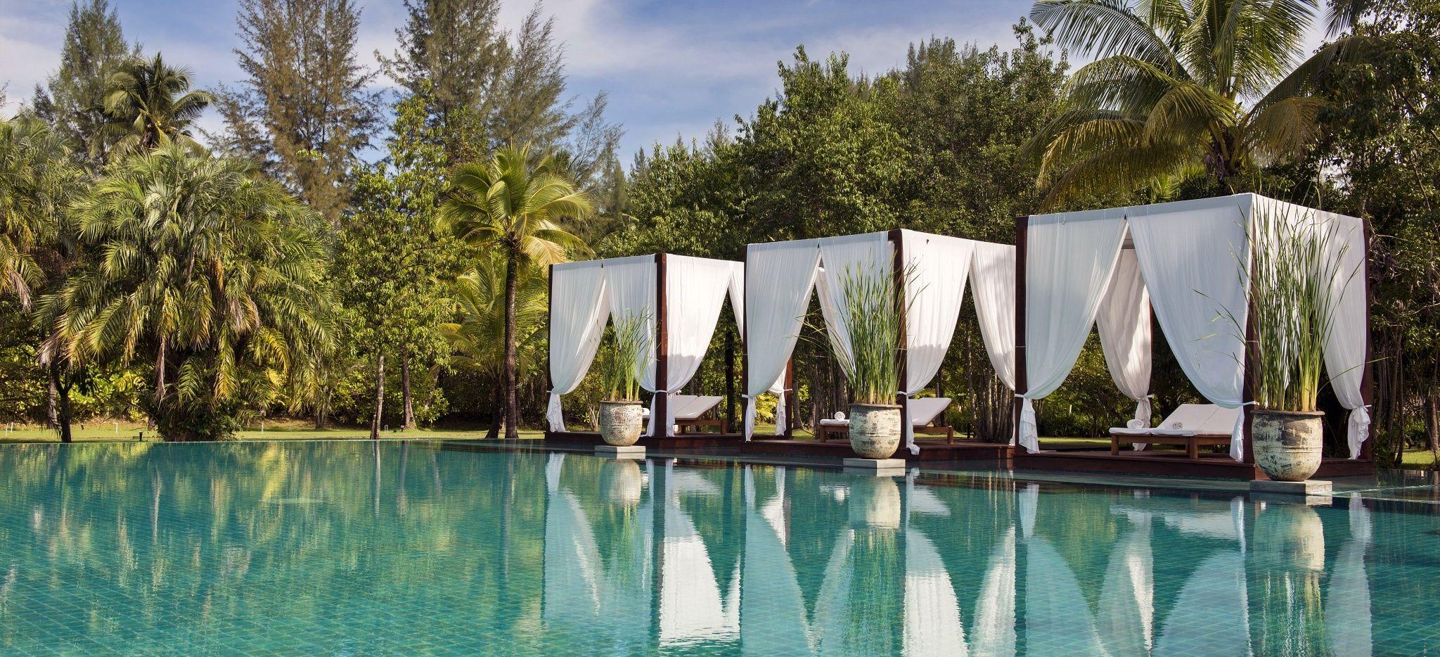 """Ein weitläufiger Pool mit Baliliegen, im Hotel """"The Sarojin"""""""