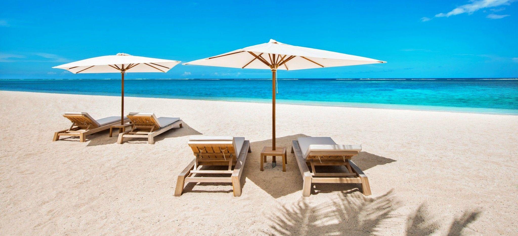 Zwei Sets Strandliegen mit Sonneschirmen am Strand auf Mauritius