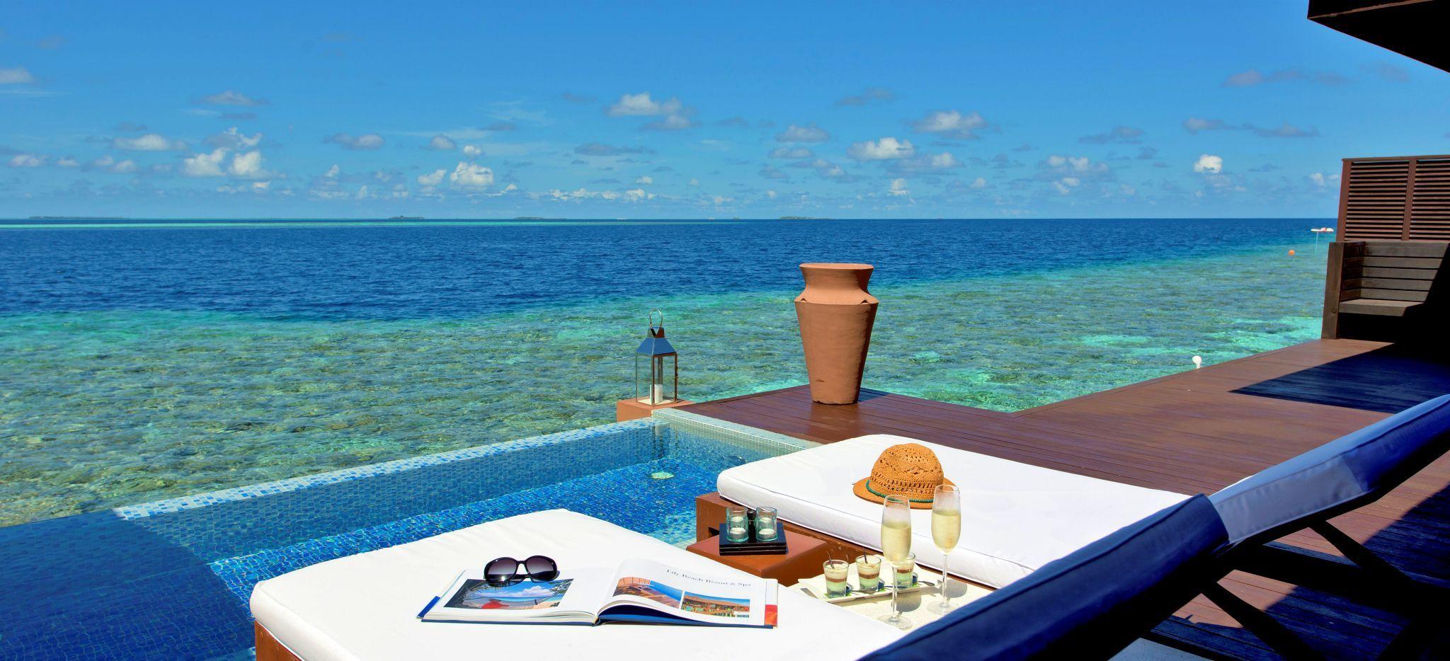 """Zwei Strandliegen mit Magazinen und Champagner auf der Terrasse einer Wasservilla des Hotels """"Lily Beach"""""""