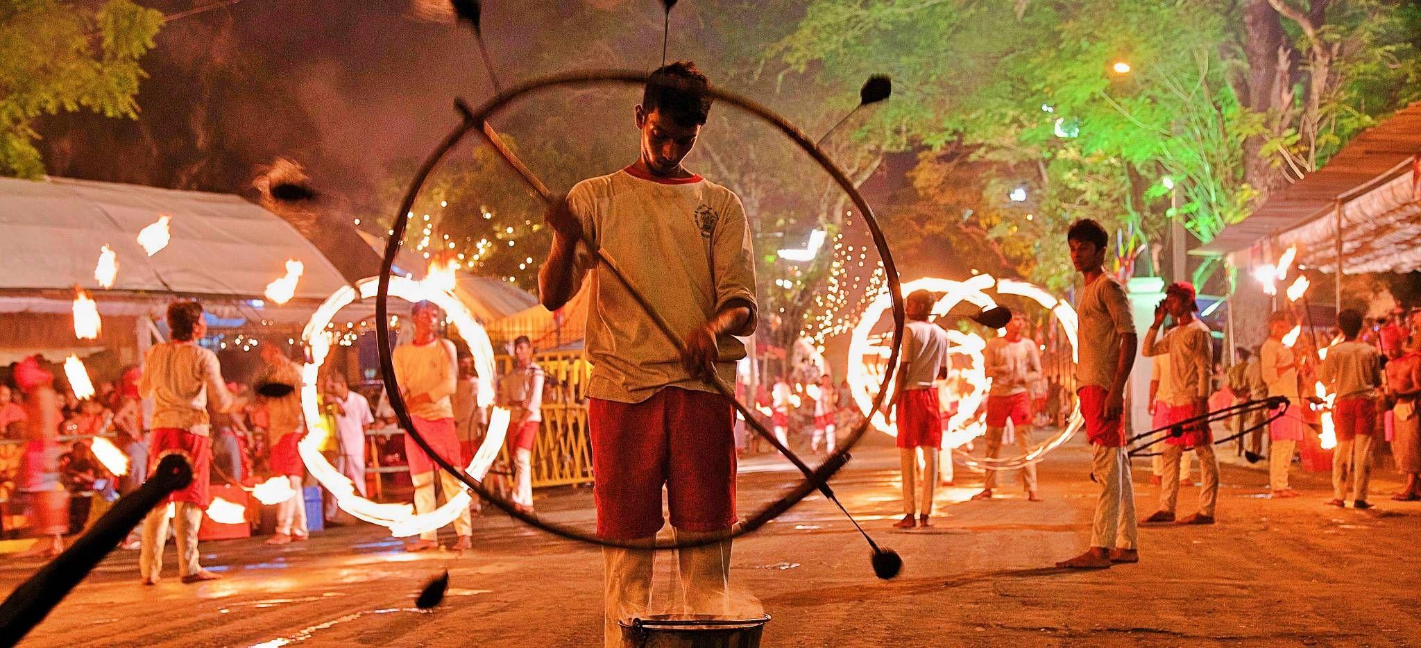 Junge Männer üben mit Feuerrädern auf Sri Lanka