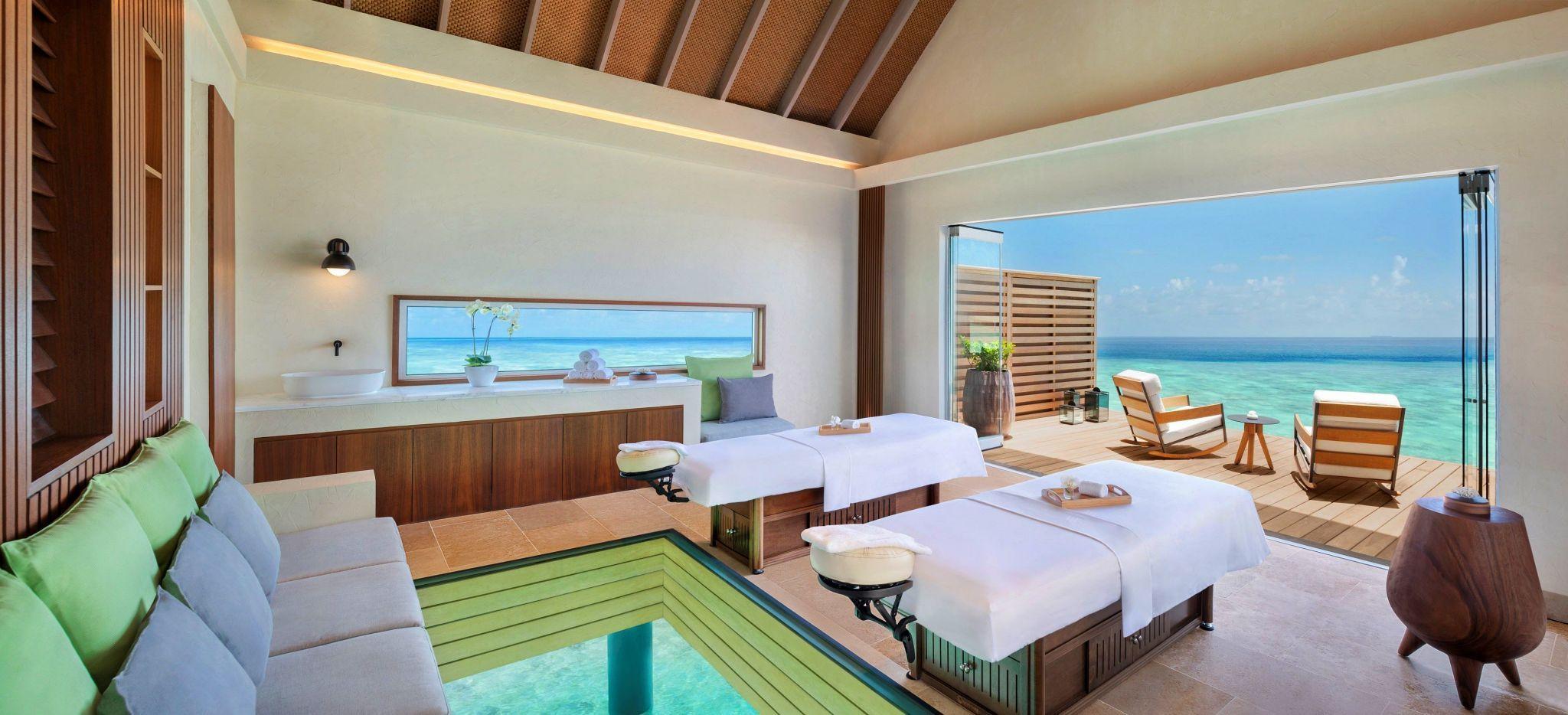 Der Spa-Bereich einer Overwater Spa Villa mit zwei Massageliegen mit Blick auf das Meer