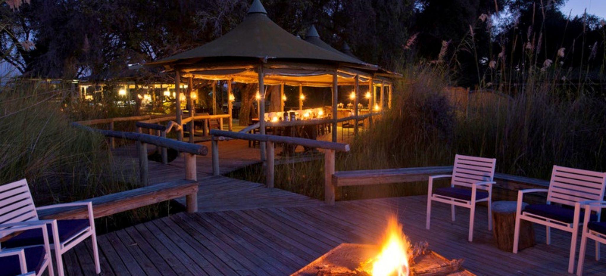 """Zentrale Feuerstelle des """"Little Vumbura Camp"""" in Botswana, das Hotel im Hintergrund"""