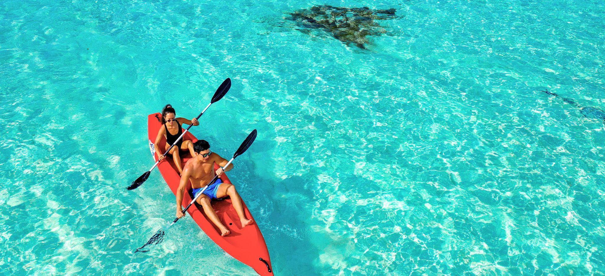 Ein Paar in einem Kajak im flachen, türkisblauen maledivischem Meer