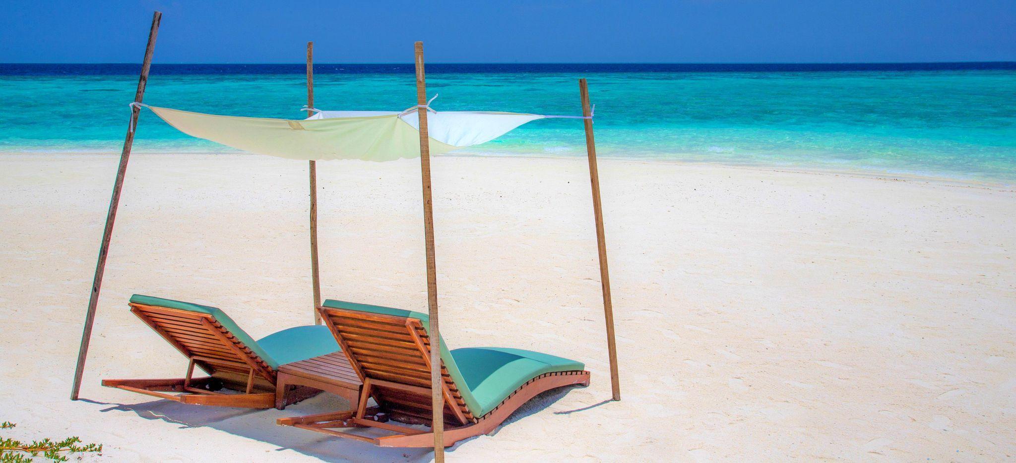 Zwei Strandliegen mit Sonnensegeln an einem unberührten Malediven-Strand