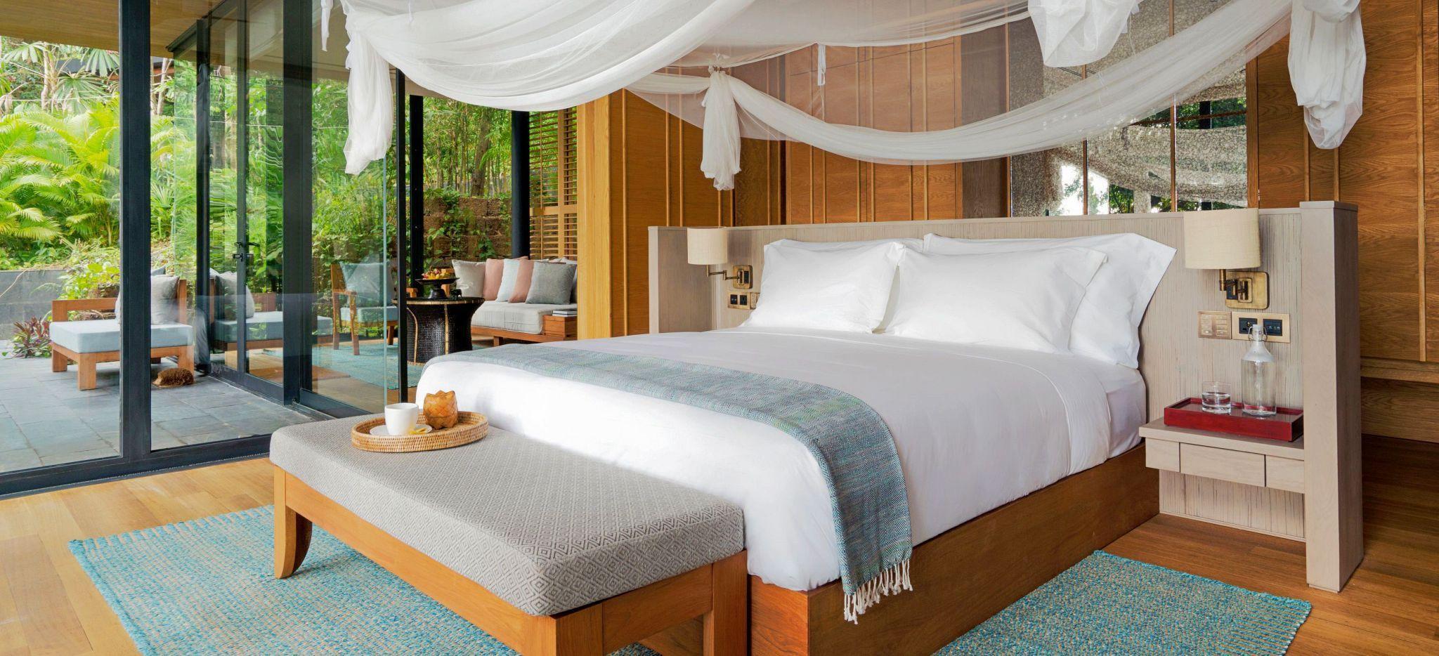 Bett vor einer Glasfront, durch die der Dschungel sichtbar ist, Hotelzimmer Ocean Pool Villa Suite im Hote Six Senses Krabey Island