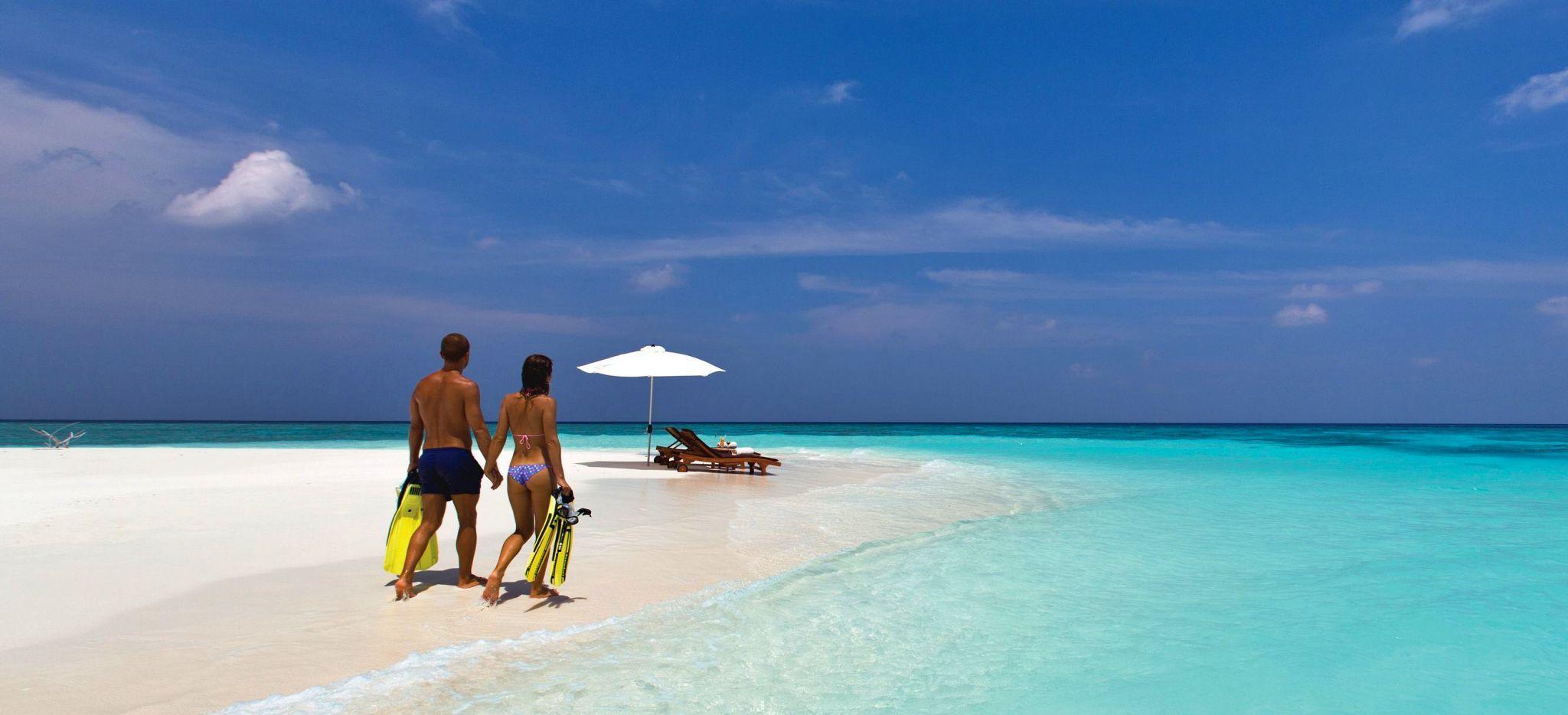 Ein Paar mit Flossen an einem eigenen Strand auf den Malediven. Ein Picknickplatz mit Sonneschirm