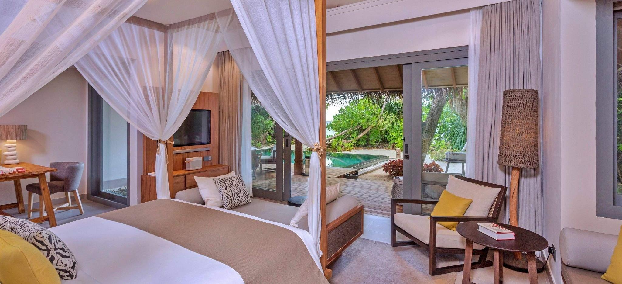 Eine Schlafzimmer mit Himmelbett und Blick auf den umliegenden Dschungel, im Hotel Vakkaru, Malediven