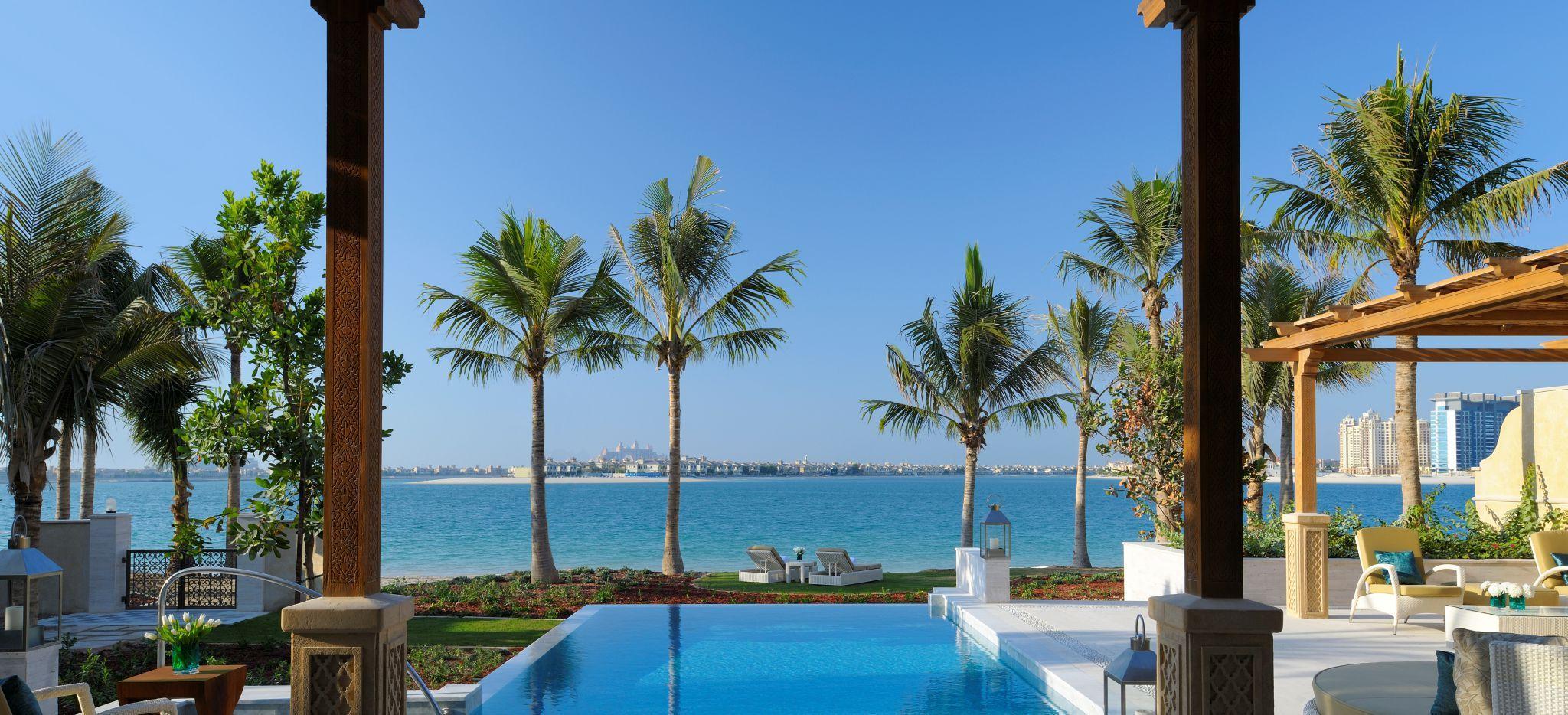 """Blick auf das Meer von der """"Pool Villa"""" aus. Blick über den Pool mit Palmen vor dem Strand"""